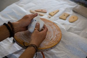 Cropped hand on craftsperson making clay sculpture
