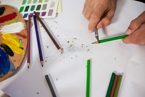 Man sharpening colored pencil in drawing class