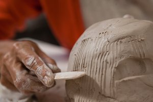 Mid-section of woman shaping a molded clay