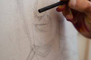 Painter drawing sketch on canvas