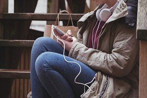 Woman using mobile phone while listening to music on headphones