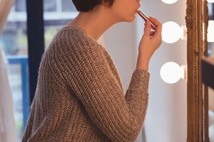 Woman applying lipstick at home