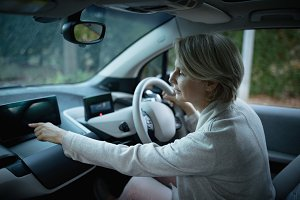 Woman using digital tablet while driving car