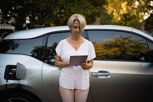 Woman using digital tablet near car