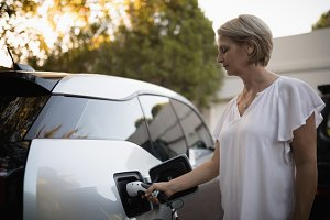 Woman charging electric car