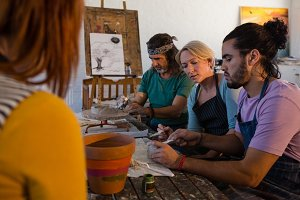 Teacher guiding students making clay products