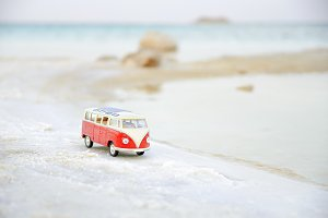 Toy car, model bus park in the sand near sea. Travel concept. Copy space