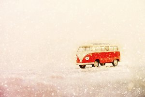 Christmas, new year, winter concept, blurred snow background. Miniature model car in snow. Glitter background. Present, gift, card. Copy space