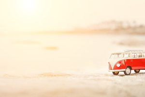 Toy car, model bus park in the sand near sea. Travel concept. Copy space. Sunny day