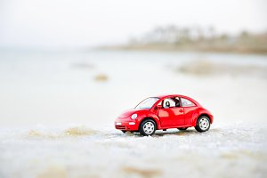 Travel concept. Red model toy car on sand near seaside. Copy space