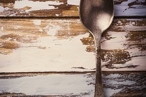 Metal spoon on old wooden grunge background