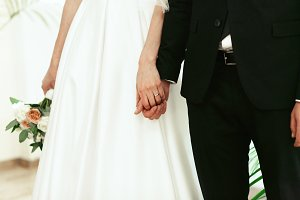 Bride and groom hold hands together