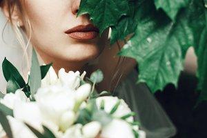 Dark green leaves hide bride`s face