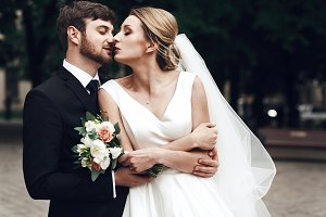 Bearded groom hugs bride tender