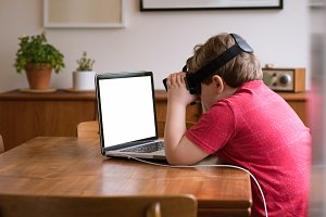 Boy wearing vr glasses while using laptop computer