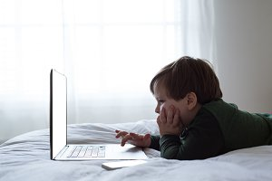 Side view of boy using laptop while lying on bed