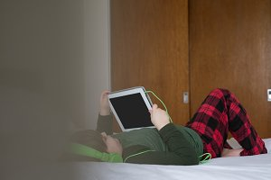 Boy using tablet computer while lying on bed