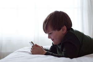 Side view of smiling boy using smart phone while lying on bed