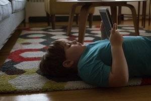 Side view of boy using digital tablet while lying on carpet