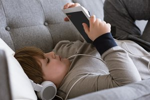 Close up of boy wearing headphones while using digital tablet