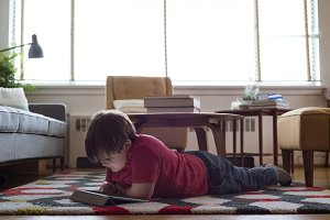 Boy using tablet computer while lying on carpet