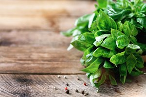 Green fresh organic basil on wooden background with copyspace. Herbs and spices for cooking