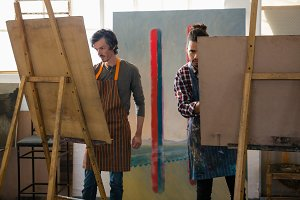 Male artists painting on easel
