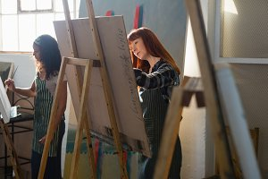 Women painting on easel