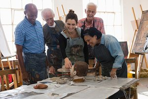 Smiling teacher with senior friends looking at clay structure
