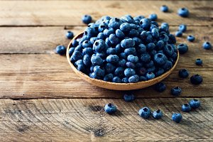Blueberries on wooden table. Blueberry bowl on vintage background with copyspace. Berries frame, healthy food concept