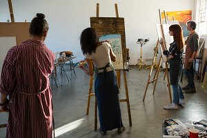 Adult students painting on artists canvas