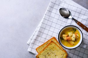 Cup of squash creamy vegetable vegetarian pumpkin carrot soup with bread crachers on light background, copy space for your text