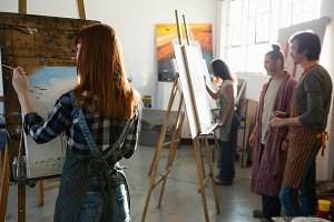 Adult students painting in art studio