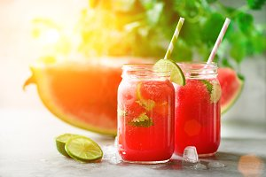 Fresh red watermelon slice and smoothie in glass jar with straw, ice, mint, lime on light background, copy space, sunlight