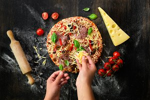 Girl hands making, decopating, preparing pizza with basil leaves on dark background. Top view, copy space