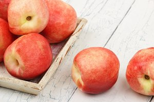 Ripe red peaches in the tray on the white wooden table