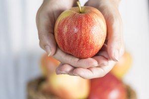 Female hands offering an apple