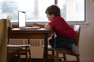 Side view of boy using laptop while kneeling on chair