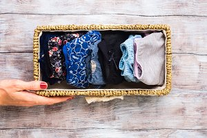 Woman panties in basket on wooden background