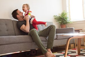 Cheerful girl with father playing on sofa