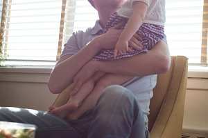 Man carrying daughter while sitting on chair by window