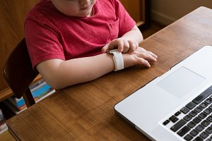 High angle view boy using smart watch while sitting by laptop
