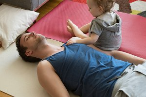 High angle view of girl sitting by father exercising on exercise mat