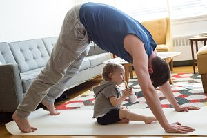 Daughter sitting below father practicing downward facing dog position