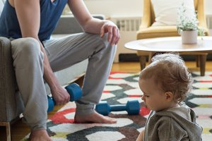 Man looking at daughter holding dumbbells