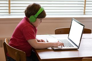 Side view of boy wearing headphones while using laptop
