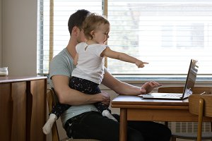 Girl gesturing while father using laptop
