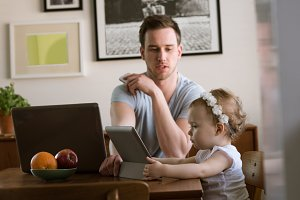 Father showing tablet computer to girl