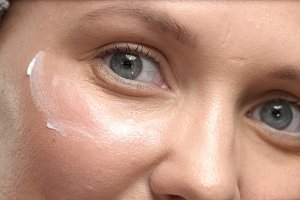 closeup of 30's woman's eue with a eye cream massage it and rub it