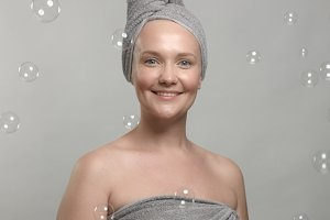 30's woman wears a towel after bath surrounded by soap bubbles